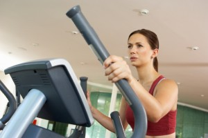 Woman On Cross Trainer Machine In Gym