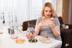 Young pregnant woman trying to decide what cookie to eat, sitting at the kitchen table full of sweets