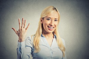 Closeup portrait, young excited woman, making five times sign gesture with hand fingers, isolated grey wall background. Positive human emotion facial expression feeling, attitude, symbol body language