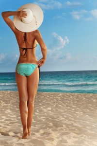 Nice beautiful attractive woman's back standing on the beach and watching the ocean
