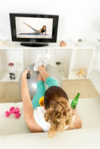Lazy woman in sport clothing sitting front of the TV and doesn't wont to exercise.