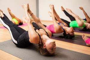 Group of women following their instructor during an authentic yoga class