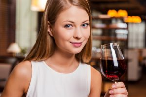 Beauty with wine. Beautiful young woman holding glass with red wine and smiling while sitting at the restaurant
