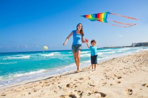 Smiling mother and happy son holding arms and flying kite in the sky during sunny day on beach coast and ocean waves
