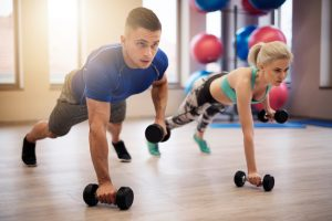 Couple making push ups with weights