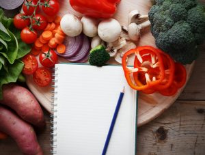 Blank shopping list with pencil surrounded by fresh veggies