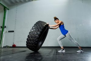 Young girl flipping tire at the gym